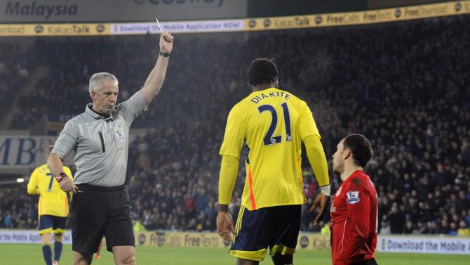 Cardiff City's Mutch is booked by referee Foy after appearing to dive in the penalty box during a English Premier League soccer match in Cardiff