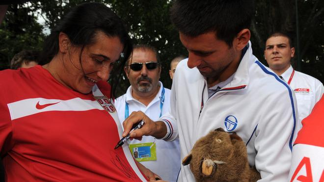 Novak Djokovic Of Serbia Signs AFP/Getty Images