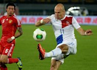Netherlands Arjen Robben (R) takes a shot at goal against China during a friendly in Beijing on June 11, 2013. Goals from Robin van Persie and Sneijder after China were reduced to ten men early in the first half saw Holland claim an unconvincing victory in Beijing on Tuesday