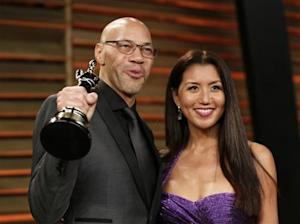 """Writer John Ridley holds up his award for best adapted screenplay for """"12 Years a Slave"""" as he arrives with his wife Gayle at the 2014 Vanity Fair Oscars Party in West Hollywood"""