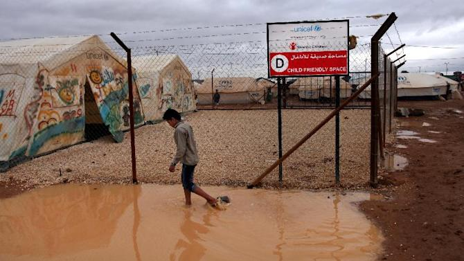 A Syrian refugee boy makes his way through water and mud, next to a UNICEF school at Zaatari Syrian refugee camp, near the Syrian border in Mafraq, Jordan, Tuesday, Jan. 8, 2013. Syrian refugees in a Jordanian camp attacked aid workers with sticks and stones on Tuesday, frustrated after cold, howling winds swept away their tents and torrential rains flooded muddy streets overnight. Police said seven aid workers were injured. (AP Photo/Mohammad Hannon)