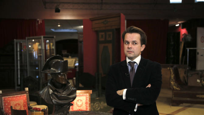 "In this photo taken Wednesday, Nov. 28, 2012, auction house associate Jean-Christophe Chataigniera poses for a photograph next to a letter dictated and signed by Napoleon in secret code that declares his intentions ""to blow up the Kremlin"" during his ill-fated Russian campaign is displayed in Fontainebleau, outside Paris. The rare letter, written in unusually emotive language, sees Napoleon complain of harsh conditions and the shortcomings of his grand army. The letter goes on auction Sunday, Dec. 2, 2012. (AP Photo/Christophe Ena)"