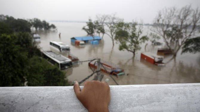 From a flyover, a young Indian girl watches buses and trucks submerged in the rising water of the Yamuna River in New Delhi, India, Wednesday, June 19, 2013. India's prime minister said Wednesday that the death toll from flooding this week in the northern state of Uttrakhand had surpassed 100 and could rise substantially. The flooding has affected several states and the capital New Delhi where nearly 2,000 people have been evacuated to government-run camps on higher ground. Authorities there said the situation would ease as the level of the Yamuna River was expected to start receding Thursday afternoon. (AP Photo/Tsering Topgyal)