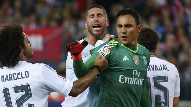 Real Madrid's goalkeeper Keylor Navas is congratulated after saving a penalty kick during their Spanish first division derby soccer match in Madrid