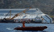 A man in a rigid inflatable boat passes by as salvage members work on a platform after removing a piece of the rock on the side of the stranded Costa Concordia cruise ship near the harbour of Giglio Porto, in July