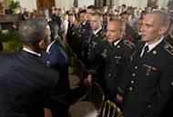 US President Barack Obama shakes hands with active duty US service members, after they became US citizens during a naturalization ceremony in the East Room of the White House in Washington, DC, July 4, 2012