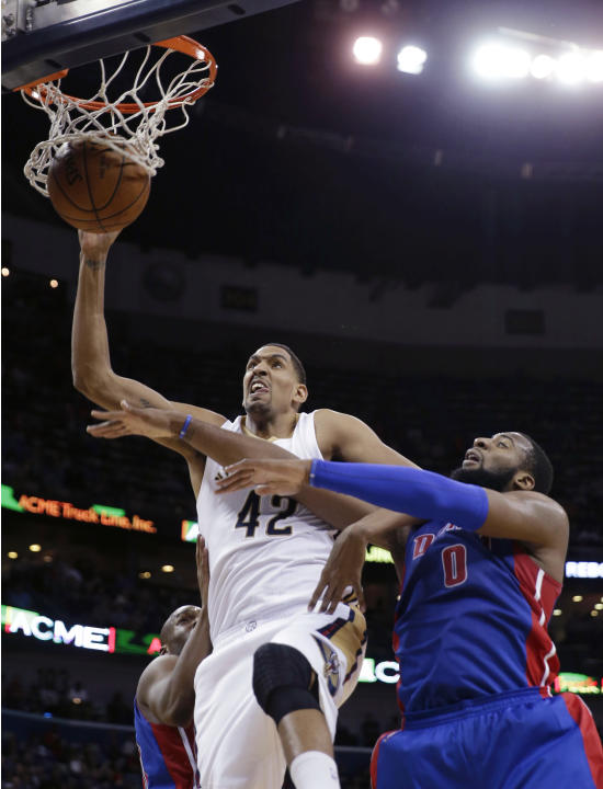 New Orleans Pelicans center Alexis Ajinca (42) dunks next to Detroit Pistons center Andre Drummond (0) during the second half of an NBA basketball game Wednesday, March 4, 2015, in New Orleans. The Pe