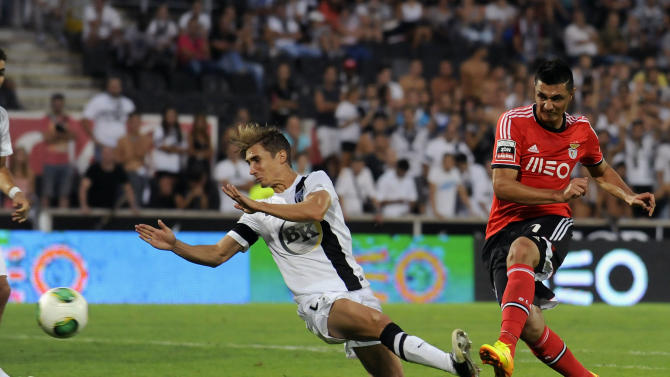 Benfica's Oscar Cardozo, right, scores past Vitoria Guimaraes' Pedro Correia, left,  in a Portuguese League soccer match at D. Afonso Henrique stadium in Guimaraes, Portugal, Sunday, Sept. 22, 2013