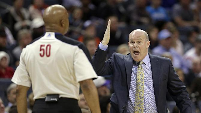 Charlotte Bobcats head coach Steve Clifford, right, argues a call with referee Olandis Poole, left, during the first half of an NBA basketball game against the Milwaukee Bucks, Monday, Dec. 23, 2013, in Charlotte, N.C