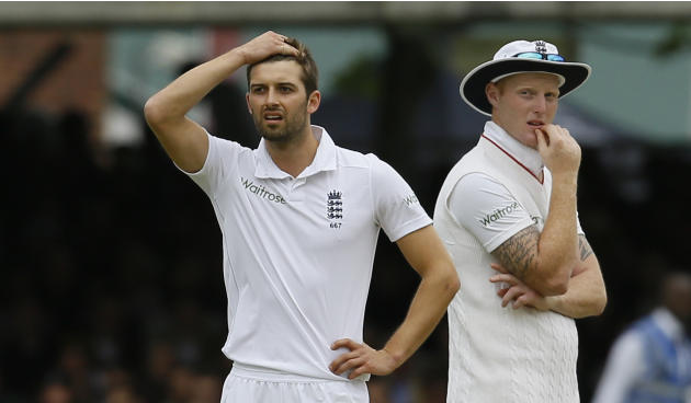 England's bowler Mark Wood, left, reacts as his teammate Ben Stokes looks on as a review shows that he had bowled a no ball to New Zealand's Martin Guptill, who had been caught at slip, but wa