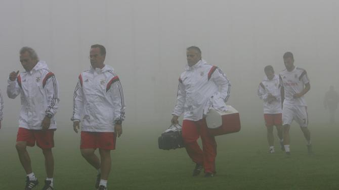 Benfica's team members leave the pitch in fog during the Portuguese Premier League soccer match between Uniao Madeira and Benfica at Madeira stadium in Funchal