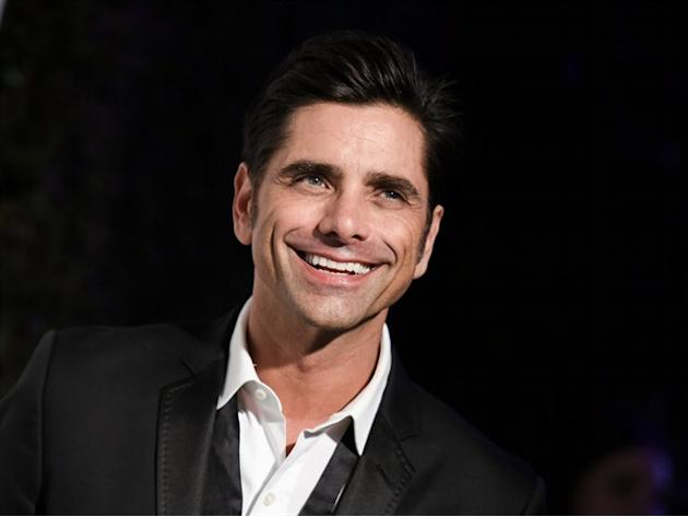 FILE - In this Feb. 22, 2015 file photo, John Stamos arrives at the 87th Academy Awards - 2015 Elton John AIDS Foundation Oscar Party in West Hollywood, Calif. Stamos says he's on board for a 13-e