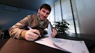 A handout picture taken and released on February 7, 2013 by Barcelona shows Lionel Messi signing his new contract with the club. Messi has extended his contract until 2018