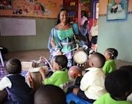 """Talking drummer Aralola Olamuyiwa, popularly known as Ara, teach children how to play the talking drum in a private school in Lagoson. She visits schools teaching children to play, calling it """"a way of preserving our heritage through our children who are going to be our tomorrow, our future."""""""