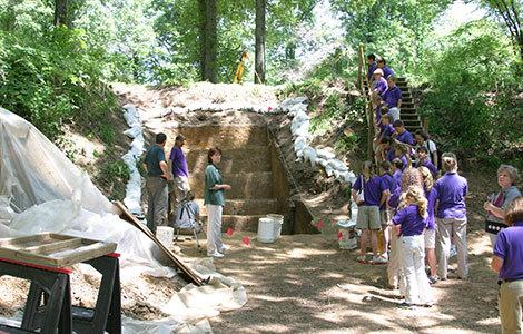 A group of school students visits the Washington University excavations of Mound A at Poverty Point.
