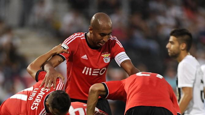 Benfica's players gather around Oscar Cardozo, below, after he was injured after scoring a goal against Vitoria Guimaraes in a Portuguese League soccer match at D. Afonso Henrique stadium in Guimaraes, Portugal, Sunday, Sept. 22, 2013. Benfica won 1-0
