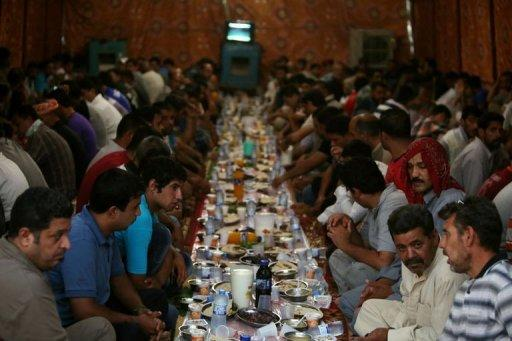 Iraqi Muslim men wait before breaking their Ramadan fast, in a meal known as Iftar, inside a tent in Baghdad, July 17