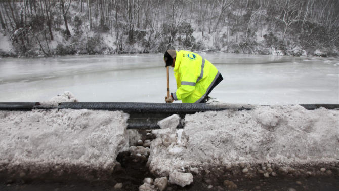 A state worker punches a hole in snow so standing water on a bridge can drain in East Lyme, Conn., Monday Feb. 11, 2013.  As electricity returns and highways reopen, some Northeast residents tried to get back to their weekday routines Monday following the massive snowstorm that had millions digging out from New York to Maine.   (AP Photo/Robert Ray)