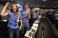 NASA's Kelley Clarke (L) celebrates as the first pictures appear on screen after the Curiosity rover successfully lands on Mars, breaking new ground in US-led exloration of the red planet