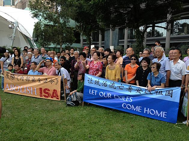 Attendees pose with former ISA detainees behind banners calling for the abolishment of the Act, as well as for the safe return of exiled Singaporeans. (Yahoo! photo)
