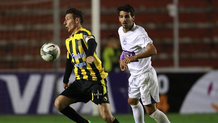 Bolivia's The Strongest's Pablo Escobar, left, controls the ball as Uruguay's Defensor Sporting's Mathias Cardaccio looks on at a Copa Libertadores soccer match in La Paz, Bolivia, Thursday, April 17, 2014