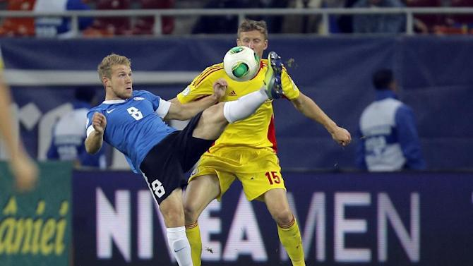 Henri Anier, left, of Estonia and Dorin Goian, right, of Romania challenge for the ball during the World Cup Group D qualifying soccer match at the National Arena stadium in Bucharest, Romania, Tuesday, Oct. 15, 2013