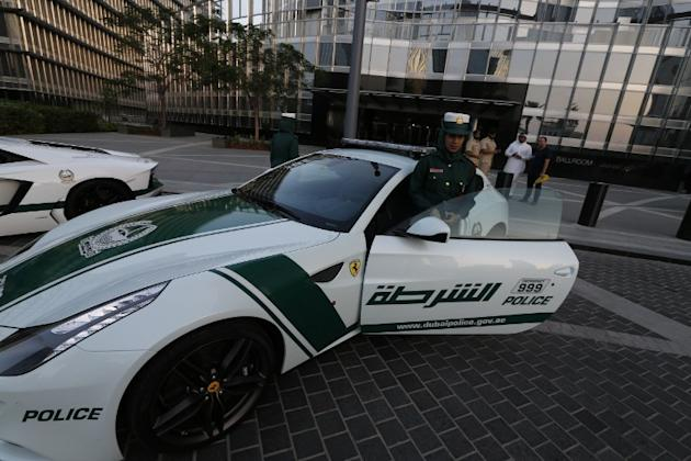 An Emirati female police officer poses in front of a Ferrari police vehicle on April 25, 2013 in the Gulf emirate of Dubai. Dubai police showed off a new Ferrari they will use to patrol the city state
