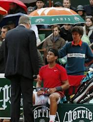 Spain's Rafael Nadal talks with the referee prior to the rain interruption during his French Open men's singles final against Serbia's Novak Djokovic at Roland Garros in Paris on June 10