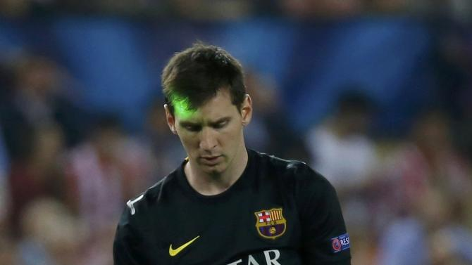 A laser is seen projected on the head of Barcelona's Messi during his team's match against Atletico Madrid in their Champions League quarter-final second leg soccer match in Madrid