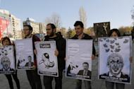 "Members of the Turkish Youth Union hold cartoons depicting Turkey's Prime Minister Recep Tayyip Erdogan during a protest against a ban on Twitter, in Ankara, Turkey, Friday, March 21, 2014. Turkey's attempt to block access to Twitter appeared to backfire on Friday with many tech-savvy users circumventing the ban and suspicions growing that the prime minister was using court orders to suppress corruption allegations against him and his government. Cartoon second right reads: Erdogan, left, to his Ankara Mayor Melih Gokcek "" we will rip out the roots of Twitter."" Gokcek: ""don't say it.""(AP Photo/Burhan Ozbilici)"