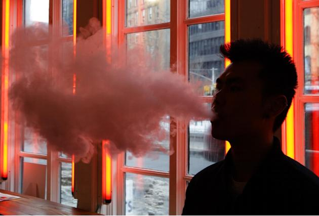 FILE - In this Feb. 20, 2014, File photo, a patron exhales vapor from an e-cigarette at the Henley Vaporium in New York. The first peek at a major study of how Americans smoke suggests many use combin