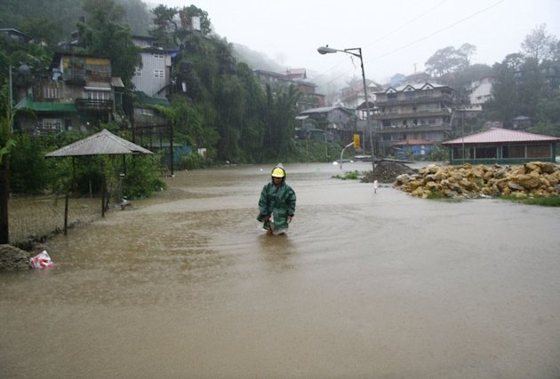 Illustration: A resident wades on a flooded street in camp Lagoon in Baguio, Trinidad province, north of Manila on August 15, 2012, after tropical Storm Kai-tak hit Luzon