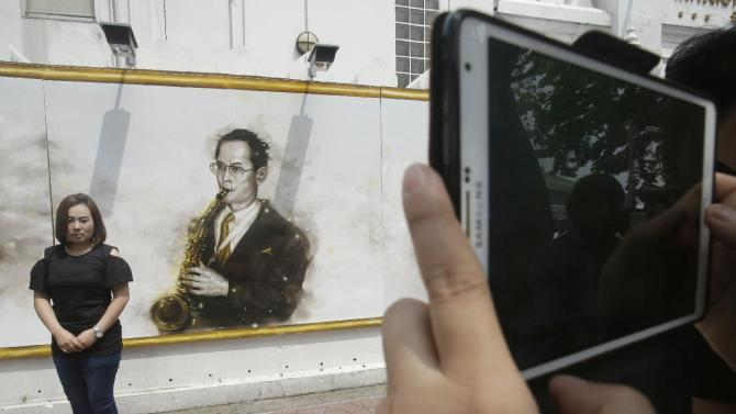 People take a picture in front of a drawing portrait of the late Thai King Bhumibol Adulyadej in Bangkok, Thailand, Tuesday, Oct. 18, 2016. Aside from his kingly duties - and they were immense - Thailand's late King Bhumibol Adulyadej took time during his 70-year reign to compose music (and jam with some of the world's jazz legends), build sailing craft (and win an international yachting race), paint surrealistic oils and have some 20 patents registered for an assortment of inventions. (AP Photo/Sakchai Lalit)