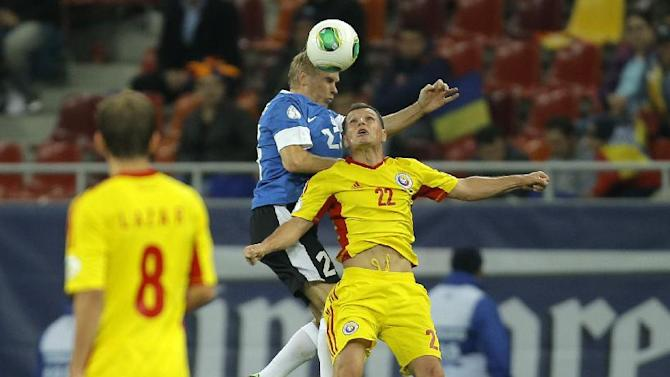 Taijo Teniste, left, of Estonia and Gheorghe Bucur of Romania, right, jump for a header during the World Cup Group D qualifying soccer match at the National Arena stadium in Bucharest, Romania, Tuesday, Oct. 15, 2013