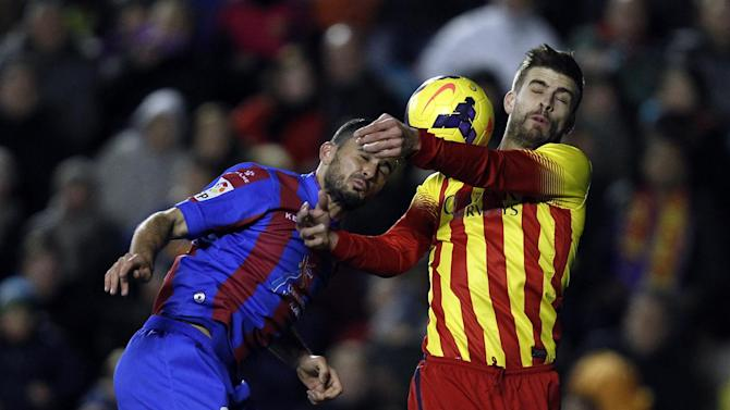 Barcelona's Gerard Pique, right, duels for the ball with Levante's Vyntra from Czech Republic during their La Liga soccer match at the Ciutat de Valencia stadium in Valencia, Spain, Sunday, Jan. 19, 2014
