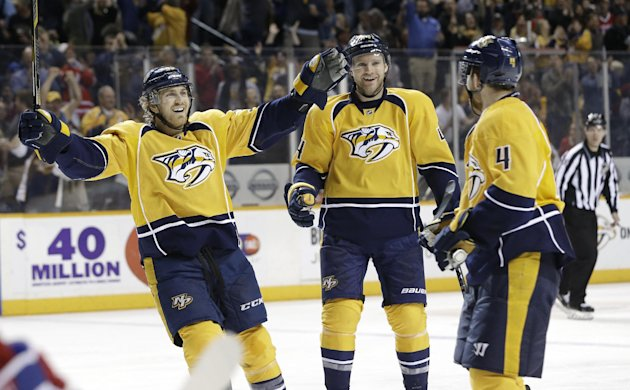 Nashville Predators' Colin Wilson, left, and Cody Franson, center, celebrate with Ryan Ellis (4) after Ellis scored a goal against the Montreal Canadiens in the third period of an NHL hockey game Tuesday, March 24, 2015, in Nashville, Tenn. (AP Photo/Mark Humphrey)