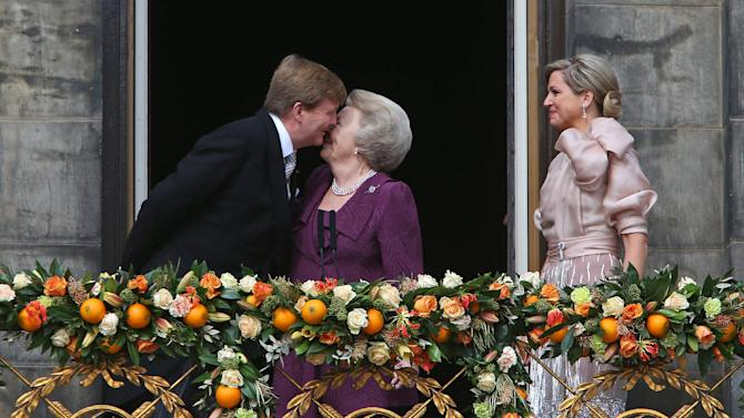 Dutch King Willem-Alexander kisses his mother Princess Beatrix as Queen Maxima looks on from the balcony of the Royal Palace in Amsterdam, The Netherlands, Tuesday April 30, 2013. Around a million people are expected to descend on the Dutch capital for a huge street party to celebrate the first new Dutch monarch in 33 years. (AP Photo/Dusan Vranic)