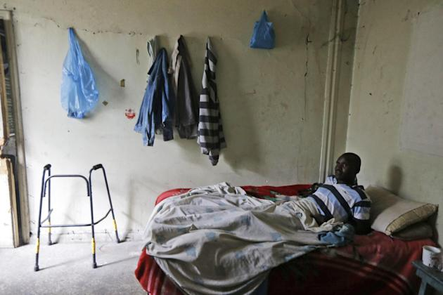 Sudanese migrant Abdallah Abdalrahman, 35, injured in a car accident in an effort to enter the port and travel illegally to Italy, lays on the bed, at an abandoned old textile factory in the southern
