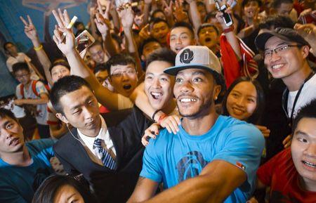 NBA Chicago Bulls' basketball player Rose poses for a selfie with Chinese fans during a fans meeting event in Guangzhou