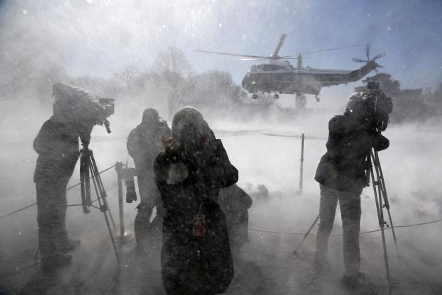 Reporters are whipped by blowing snow as Obama departs via the Marine One helicopter from the White House in Washington