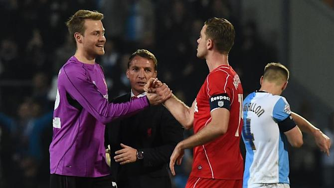 Liverpool's manager Brendan Rodgers (2nd L) celebrates on the pitch with goalkeeper Simon Mignolet (L) and midfielder Jordan Henderson after their English FA Cup quarter-final 2nd leg match against Blackburn Rovers, in Blackburn, on April 8, 2015