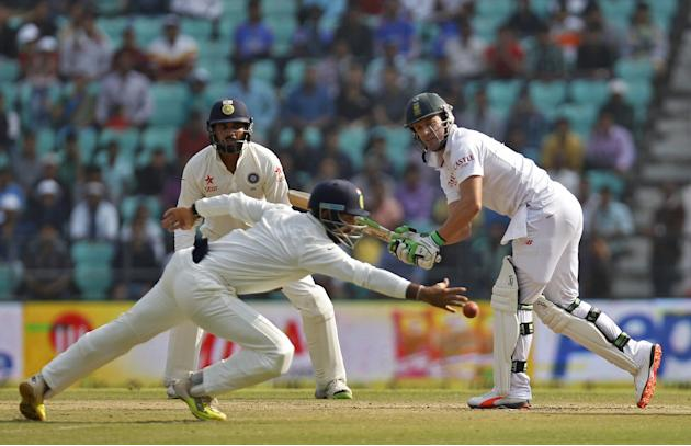 South Africa's Villiers plays a shot as India's Pujara dives to catch the ball as India's Vijay watches during the third day of their third test cricket match in Nagpur