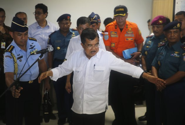 Indonesia's Vice President Jusuf Kalla gestures before deliver a speech in front of family members of passengers onboard AirAsia flight QZ8501 at a waiting area in Juanda International Airport, Surabaya December 29, 2014. A missing AirAsia jet carrying 162 people could be at the bottom of the sea after it was presumed to have crashed off the Indonesian coast, an official said on Monday, as countries around Asia sent ships and planes to help in the search effort. REUTERS/Beawiharta (INDONESIA - Tags: DISASTER POLITICS TRANSPORT)