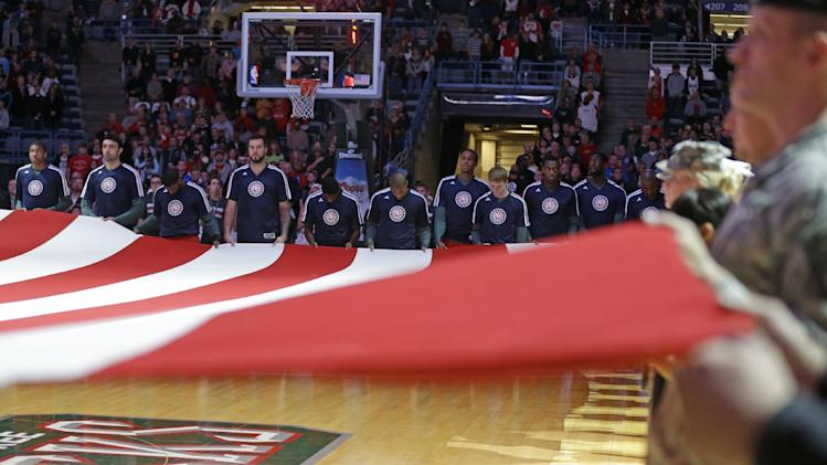 Milwaukee Bucks players hold a U.S. flag during the national anthem before an NBA basketball game against the Dallas Mavericks on Saturday, Nov. 9, 2013, in Milwaukee