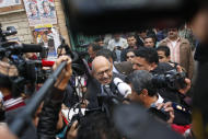 Reporters flank Egyptian reform leader and Nobel Peace Prize laureate Mohamed ElBaradei while leaving a polling station after voting, in Giza, Egypt Thursday, Dec. 15, 2011. Islamists and liberals made accusations of abuses during the second round of Egypt's first post-Hosni Mubarak parliamentary elections as voters cast ballots Thursday in mostly rural parts of the country. (AP Photo/Nasser Nasser)