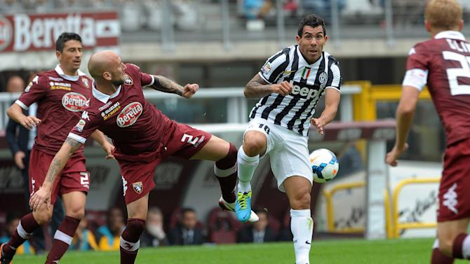 Torino's Guillermo Daniel Rodriguez, left, of Uruguay, vie for the ball with Juventus Argentine striker Carlos Tevez, during a Serie A soccer match between Torino and Juventus, at the Olympic stadium, in Turin, Italy, Sunday, Sept. 29, 2013. Juventus earned a narrow 1-0 win in a heated derby match at city rival Torino on Sunday, to move provisionally top of the table with Napoli. Paul Pogba scored a contentious 54th minute winner, heading in the rebound after Carlos Tevez's header came off the crossbar. There were fierce protests from Torino, however, as Tevez appeared to be offside