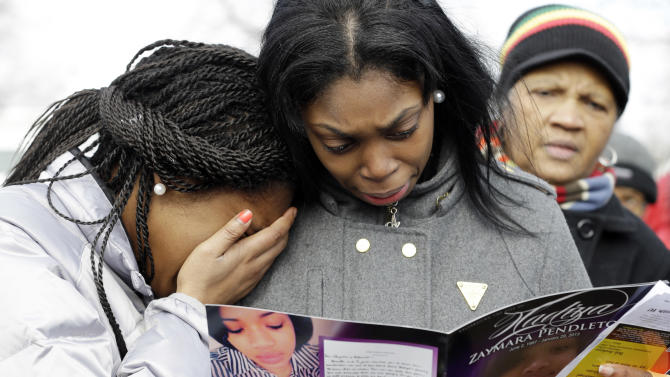 Danyia Bell, left 16, and Artureana Terrell , 16, react as they read a program for the funeral of Hadiya Pendleton outside the Greater Harvest Missionary Baptist Church after the funeral service of Hadiya Pendleton Saturday, Feb. 9, 2013, in Chicago. Hundreds of mourners and dignitaries including first lady Michelle Obama packed the funeral service Saturday for a Chicago teen whose killing catapulted her into the nation's debate over gun violence. (AP Photo/Nam Y. Huh)