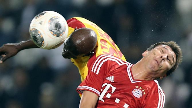 Bayern Munich's Mario Mandzukic, right, challenges for the ball with Al-Taher Sadoumba of Al-Merreikh, during their friendly soccer match, at Al-Saad stadium in Doha Thursday, Jan. 9, 2014