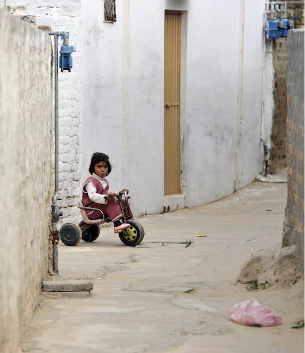 A young girl plays outside the family re