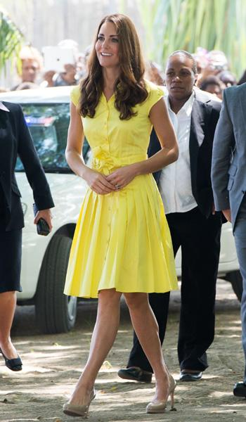 Kate wears a primrose yellow sleeveless dress from high street store Jaeger while visiting the Solomon Islands. It's super fun with the pleated skirt, cap sleeves and tied sash around the waist. Unfor